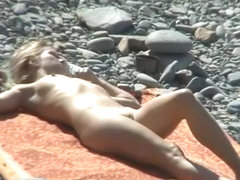 Small boobs nude woman at the rocky beach