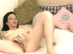Tattooed chick with big natural tits fucks her juicy cunt on the bed