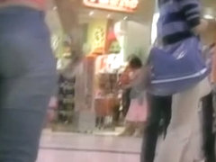 Sexy girl walking around a mall with a voyeur cam following