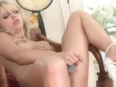 Foxy blonde Jana Jordan sits on a chair and toys her sweet fuck hole